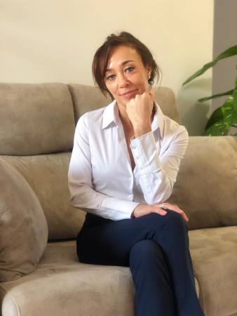 Ana Rodriguez, sentada en sofá, con las piernas cruzadas.
